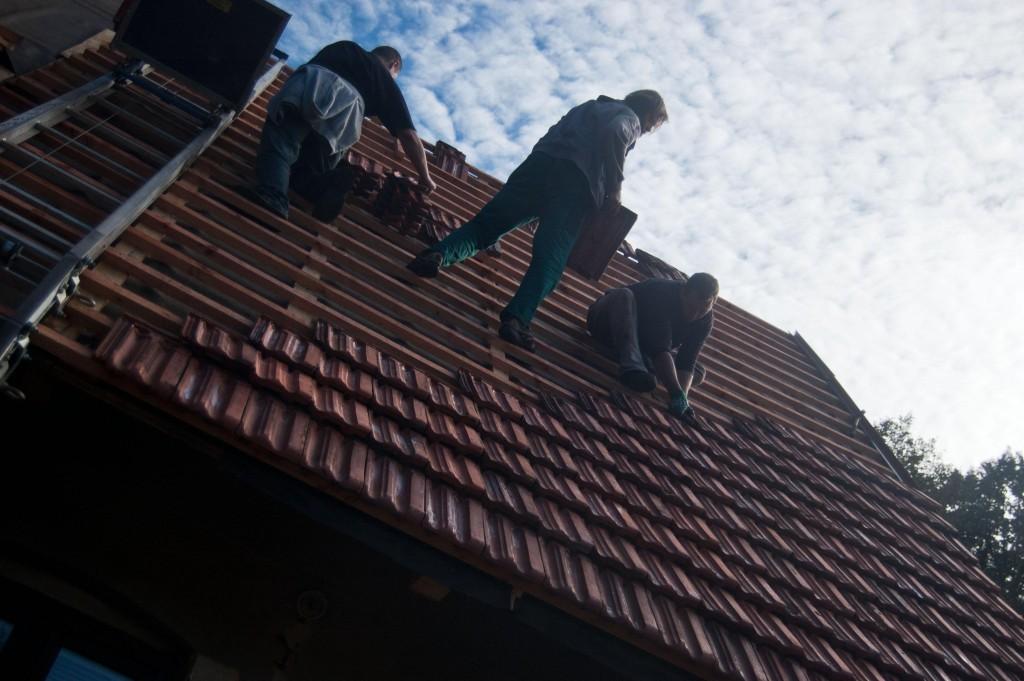 Pokládání vyčištěné a naimpregnované střešní krytiny zpět na střechu